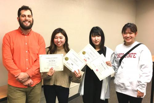 Otsuma Women's University student receive end-of-program certificates from ALCI faculty Jamie Morris