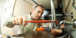 Photo of plumber using a wrench on under-sink pipes.
