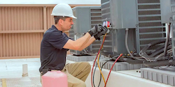 Photo of man performing maintenance on an outdoor HVAC/R unit