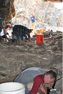 Students at the Archaeological Field School on a dig in a cavern,