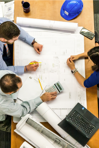 Group of engineering standing over a table holding plans and a laptop.