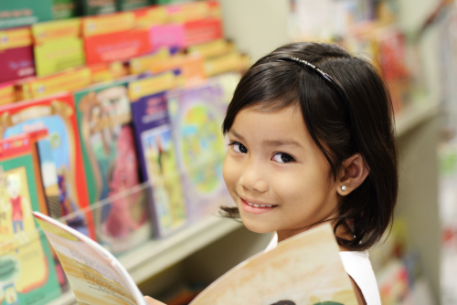Young girl in front of a shelf of books.