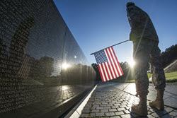 """A U.S. Army Reservist reads some of the 58,307 names etched into """"the Wall"""" of the Vietnam Veterans Memorial as the sun rises in Washington, July 22, 2015. Photo By: Army Sgt. Ken Scar"""